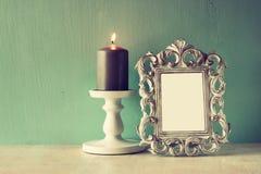 Zurückhaltendes Bild des klassischen Rahmens der Weinleseantike und brennende Kerze auf Holztisch Gefiltertes Bild Lizenzfreie Stockbilder
