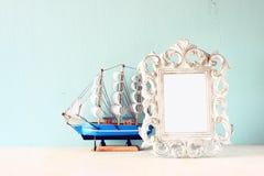 Zurückhaltendes Bild des klassischen Rahmens und des Bootes der Weinleseantike auf Holztisch Gefiltertes Bild Stockfoto