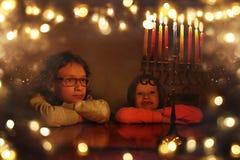 Zurückhaltendes Bild jüdischen Feiertag Chanukka-Hintergrundes mit zwei netten Kindern, die menorah traditionelle Kandelaber betr Stockbild
