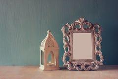 Zurückhaltendes Bild Weinleseantike der klassischen Rahmens und Laterne auf Holztisch Gefiltertes Bild Stockbilder