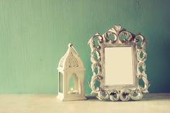 Zurückhaltendes Bild Weinleseantike der klassischen Rahmens und Laterne auf Holztisch Gefiltertes Bild Lizenzfreies Stockfoto