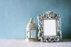 Zurückhaltendes Bild Weinleseantike der klassischen Rahmens und Laterne auf Holztisch Gefiltertes Bild Stockfoto
