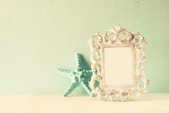 Zurückhaltendes Bild Weinleseantike der klassischen Rahmens und Starfish auf Holztisch Gefiltertes Bild Lizenzfreie Stockfotografie