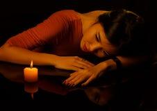 Zurückhaltendes Porträt der jungen hübschen Frau mit Kerze und reflectio Stockbild