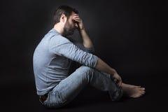 Zurückhaltendes Porträt des Mannes sitzend in der Dunkelheit und Stockfotos