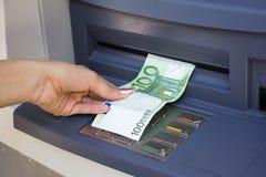 Zurücknahmegeld aus ATM heraus Stockbild