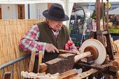 Ein Handwerker, der das Holz mit einer antiken Drehbank bearbeitet Lizenzfreie Stockfotografie