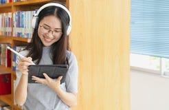 Zur?ck zu Schulbildungswissenscollege-Hochschulkonzept Studentinstudie in der Bibliothek unter Verwendung der Tablette und suchen stockfotografie
