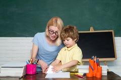Zur?ck zu Schule P?dagogischer Prozess Gro?e Studienleistung Kind und Lehrer nahe Tafel im Schulklassenzimmer lizenzfreie stockbilder