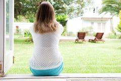 Zurück von der Frau, die draußen sitzt und schaut Lizenzfreies Stockfoto