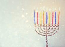 Zurückhaltendes Bild jüdischen Feiertag Chanukka-Hintergrundes mit menorah brennenden Kerzen über Funkelnhintergrund Stockfotos