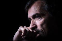 Zurückhaltendes Nahaufnahmeporträt des alten Mannes mit schwarzem Hintergrund Stockbild