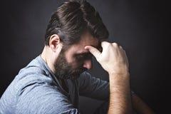 Zurückhaltendes Porträt des Mannes sitzend in der Dunkelheit und Stockfotografie