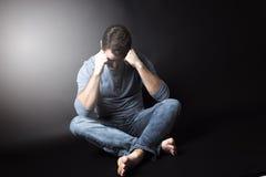 Zurückhaltendes Porträt des Mannes sitzend in der Dunkelheit und Stockbilder