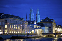 Zurich Grossmunster cathedral at night. Zurich, Switzerland - June 20, 2011: Nightly scene of the old town of Zurich along the river Limmat with the towers of Royalty Free Stock Image