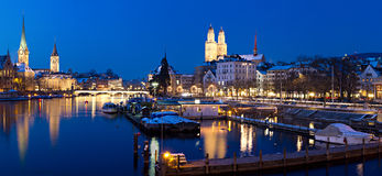 Zurich at night river view. Panorama: Zurich, swiss financial center seen from river Limmat at night with historic city center and it's churches reflecting in Stock Images