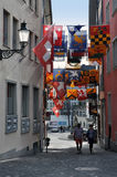 Zurich old narrow street with hanging flags. ZURICH, SWITZERLAND - APRIL 15, 2015:  Zurich old narrow street with hanging flags of different countries and Royalty Free Stock Photos