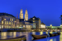Zurich old town at night. Grossmunster cathedral with river limmat and blurred boats at night in Zurich, Switzerland Royalty Free Stock Photography