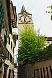 Zurich Old town street Switzerland. View of a Altstadt narrow street with St Peter`s church clock tower.The historic heart of Zurich, the Altstadt, or Old Town Stock Photos
