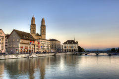 Zurich sightseeing old town at sunset. Zurich - Switzerland: Historic Grossmunster cathedral with river limmat at sunset. View over the river into the alps Royalty Free Stock Images