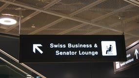 ZURICH SCHWEIZ - FÖRDÄRVA 31st, 2015: flygplatstecken till den SCHWEIZISKA affären och senator Lounge inom den slutliga byggnaden royaltyfri fotografi