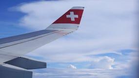 ZURICH SCHWEIZ - FÖRDÄRVA 31st, 2015: Wing View av ett flygplan under molnig blå indigoblå himmel Royaltyfria Bilder