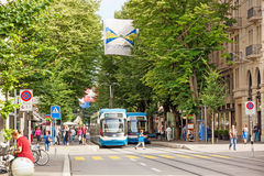 Zurich shopping street Bahnhofstrasse with tram and flag Stock Photo
