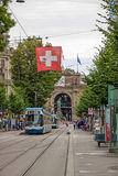 Zurich shopping street Bahnhofstrasse with tram and swiss flag Royalty Free Stock Photo