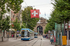 Zurich shopping street Bahnhofstrasse with tram and swiss flag Royalty Free Stock Images