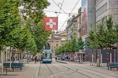 Zurich shopping street Bahnhofstrasse with tram and swiss flag Royalty Free Stock Image