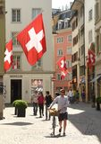 Zurich, Switzerland - June 03, 2017: People on the street of Zurich decorated with flags of Switzerland. Swiss Flags on royalty free stock photo