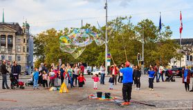 People in Zurich watching a street artist making soap bubbles. Zurich, Switzerland - 1 October, 2017: people on General Guisan quay watching a street artist Royalty Free Stock Photography