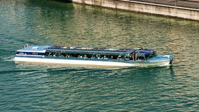 Excursion boat with tourists in Limmat River in Zurich Swiss. Zurich, Switzerland - September 2, 2016: Excursion boat with tourists in Limmat River in Zurich Royalty Free Stock Photography