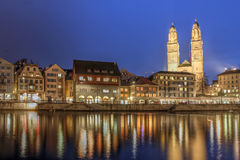 Zurich, Switzerland. Twilight scene in Zurich, Switzerland with the  city reflecting in the waters of Limmat river as it flows into the Zurich Lake. Grossmunster Stock Photo