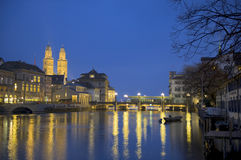 Zurich at twilight. River Limmat with Grossmunster cathedral at dusk Stock Photo
