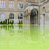 Zurich University reflection - detail. Zurich University building reflecting in a yellow water pool Royalty Free Stock Images