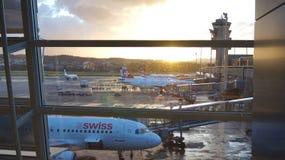 ZURIQUE, SUÍÇA - 31 de março de 2015: Opinião do aeroporto através da janela da área de espera - planos da linha aérea SUÍÇA em s Foto de Stock Royalty Free
