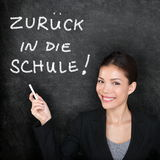 Zuruck in die Schule - German back to school. Zuruck in die Schule - German teacher woman. Back to School written in German on blackboard by female on chalkboard stock image