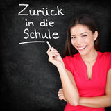 Zuruck in die Schule - German teacher back to school. Written in German on blackboard by woman teacher holding chalk. Smiling happy woman teaching German stock images