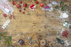 Zusätze, bereitend für Weihnachten vor Feiertagsdekorationsspielwaren, Girlanden, Lichter, Kranz über altem Weinleseholztisch stockbild