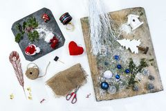 Zusätze, bereitend für Weihnachten vor Feiertagshintergrunddekorationsspielwaren, Girlanden, auf einem alten hölzernen Brett und  lizenzfreie stockbilder