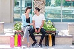 Zusammen kaufen Verbinden Sie das Sitzen auf einer Bank und das Halten des Einkaufens Lizenzfreie Stockfotos