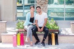 Zusammen kaufen Verbinden Sie das Sitzen auf einer Bank und das Halten des Einkaufens Stockbilder