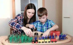 Zusammen spielen Mutter und Sohn spielen eine hölzerne Eisenbahn mit Zug, Lastwagen und Tunnel mit dem Plastiksoldatsitzen Stockfoto