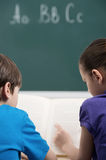 Zusammen studieren. Hintere Ansicht von zwei kleinen Mitschülern, die a lesen Stockfoto