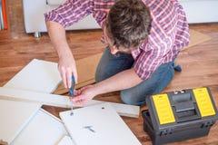 Zusammenbauende M?bel des Mannes zu Hause auf dem Boden lizenzfreie stockbilder
