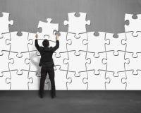 Zusammenbauende Puzzlespiele auf Betonmauer Stockfotos
