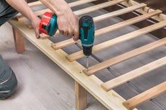 Zusammenbauende schraubende Schrauben des Tischlers des Holzmöbels Stockbilder