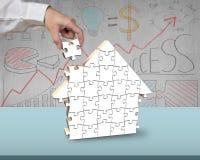Zusammenbauende weiße Puzzlespiele im Haus formen auf Schreibtisch Lizenzfreie Stockfotografie