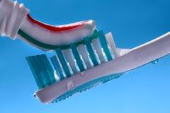 Zusammendrücken der gestreiften Zahnpasta auf Zahnbürste Lizenzfreie Stockbilder